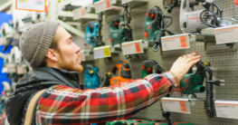 Handwerker im Baumarkt vor einer Regalwand mit Stichsägen zum Kauf